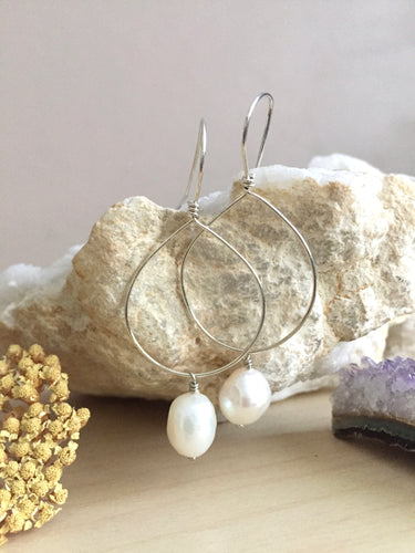 Sterling silver hoop earrings with a white freshwater pearl drop hanging from the hoop