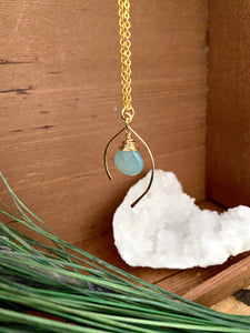 Sea Foam or Aqua blue gemstone drop wire wrapped and anclosed in an open wish bone shaped frame. Suspended from a 16 inch chain