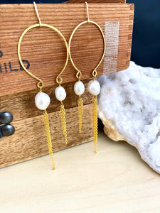 View of handmade gold and freshwater pearl boho statement earrings shown hung from a brown box.  Image shows the approximate length of the earrings and the length of the asymmetrical chain tassels