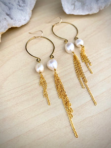 Close up of gold inverted pearl statement  earrings with long chain tassels