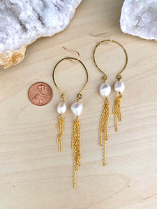 Image of asymmetrical freshwater pearl and gold tassel earrings suspended from an inverted hammered brass hoop and attached to 14kgold fill ear wires. Earring are on a table with a penny next to the earrings to show scale and size