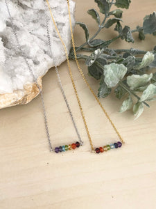 Rainbow bar necklaces laying on a table in a choice of silver or gold chain