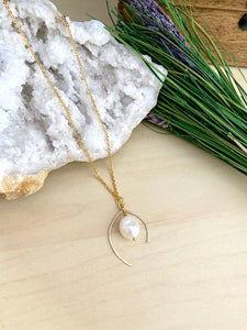 Wish bone shaped pendant necklace made from 14k gold fill wire and accompanied by a white freshwater pearl drop