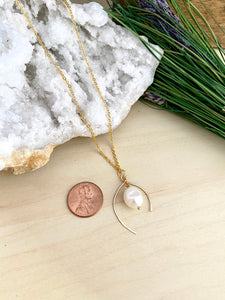 wish bone shaped gold metal frame with a freshwater pearl enclosed within in pendant frame.
