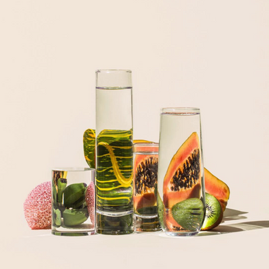 Four glasses of water at varying heights sit in front of papaya, kiwi, and other fruits. The fruit looks warped through the water glass.