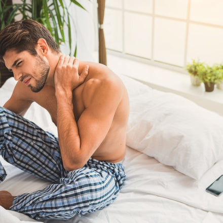 A man in bed with his shirt off pulling the back of his neck in distress
