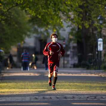 A man in a red jump suit and a face mask running on a wide sidewalk