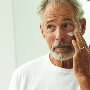 older man putting skincare on his face