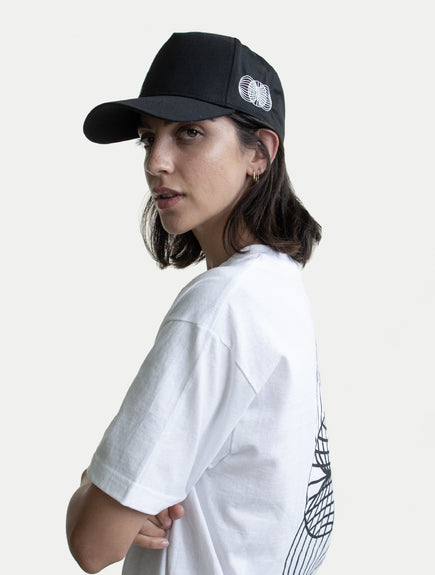 female model with black ASYSTEM hat and white t-shirt side angle