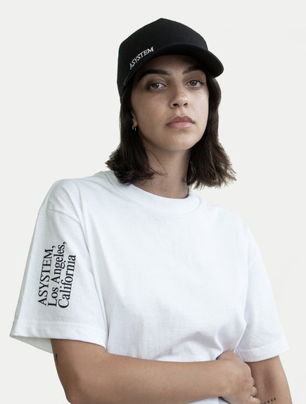 female model with black ASYSTEM hat and white t-shirt