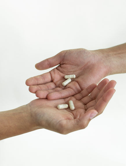 two hands with two pills on each