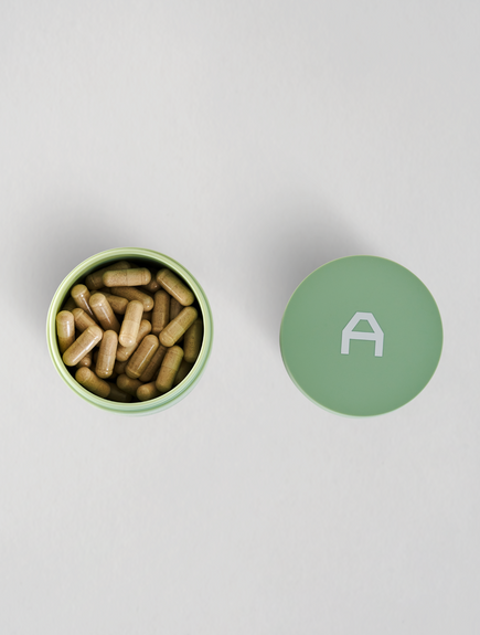 asystem anti inflammatory pills jar open with top view of pills in jar and lid to the left of it