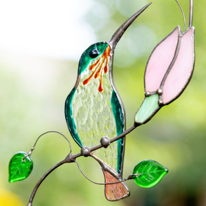 Stained glass zoomed hummingbird on the branch with pink flower