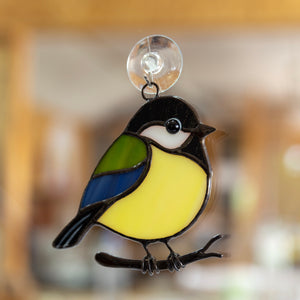 Stained glass black chickadee sitting in the branch suncatcher