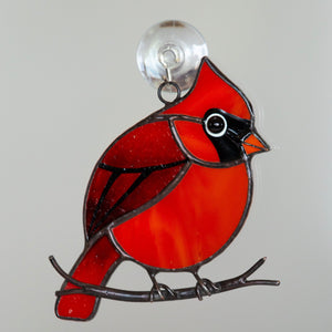 Stained glass suncatcher of a cardinal sitting on the branch