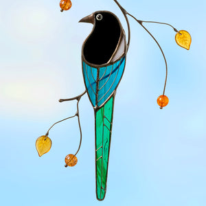 Stained glass magpie with long tail sitting on a branch suncatcher