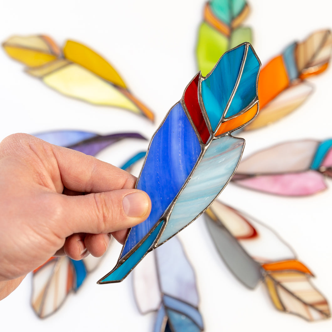 Blue stained glass feather with red and orange parts window hanghing