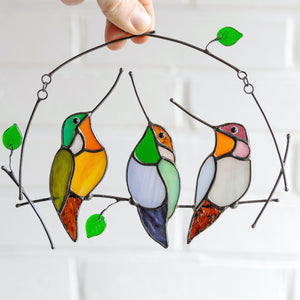 Suncatcher of three stained glass hummingbirds on the horizontal branch