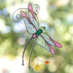 Stained glass pink dragonfly sitting on the branch window hanging