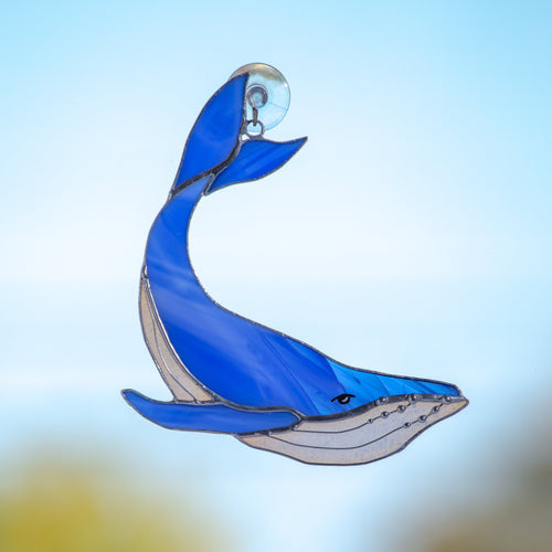 Stained glass whale suncatcher of a royal blue colour with its tail up