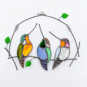 Three stained glass hummingbirds on the horizontal branch window hanging
