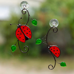 A pair of stained glass ladybugs on the branch with leaves window hanging