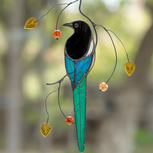 Stained glass magpie with long teal tail sitting on a branch