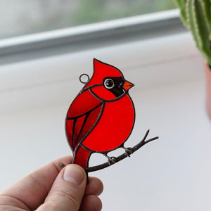 Stained glass red northern cardinal sitting on the branch window hanging