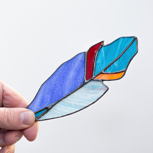 Zoomed stained glass blue feather suncatcher with shades of blue, orange and red