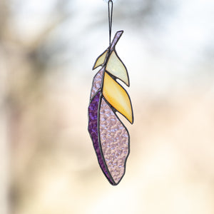 Stained glass feather suncatcher with purple and yellow accents
