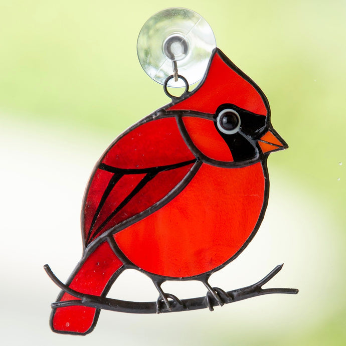 Stained glass winter redbird sitting on the branch suncatcher