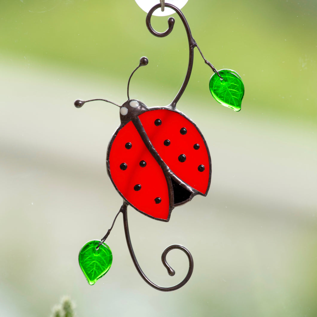 Top-view stained glass ladybug with leaves window hanging