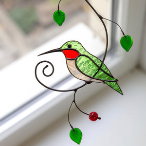 Zoomed stained glass green hummingbird on the branch window hanging