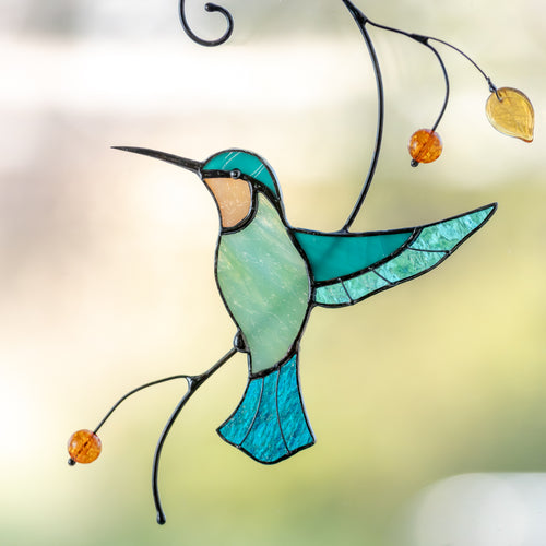Stained glass hummingbird taking off the branch window hanging