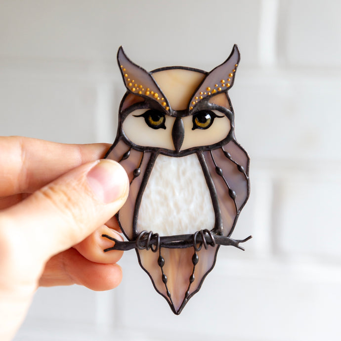 Suncatcher of a stained glass horned owl on the branch
