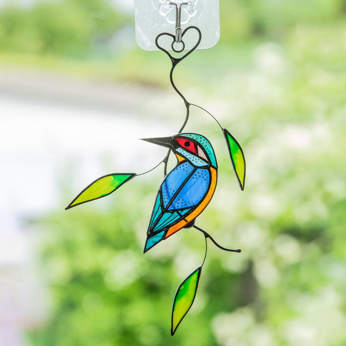 Stained glass kingfisher sitting on the branch with leaves suncatcher