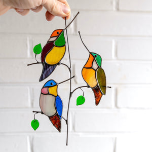 Suncatcher of three stained glass hummingbirds sitting on the vertical branch