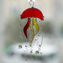 Load image into Gallery viewer, Window hanging of an orange stained glass jellyfish suncatcher with two yellow tentacles