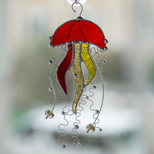Window hanging of an orange stained glass jellyfish suncatcher with two yellow tentacles