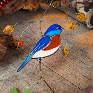 Stained glass suncatcher of a bluebird sitting on the branch