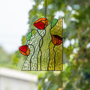 Window panel of stained glass depicting three red poppies