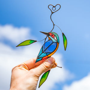 Suncatcher of a stained glass bright kingfisher with green leaves