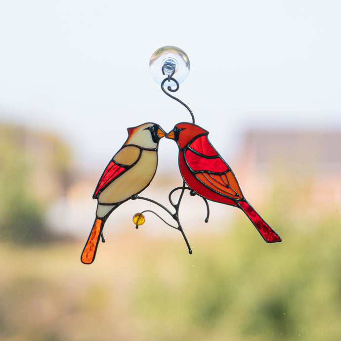 Stained glass pair of cardinals kissing each other suncatcher