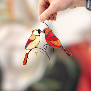 Window hanging of stained glass cardinals kissing each other