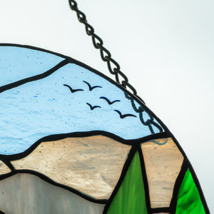 Zoomed stained glass round panel depicting lake Tahoe