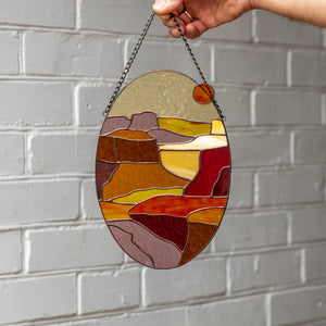 An oval panel of stained glass depicting Arizona Grand Canyon
