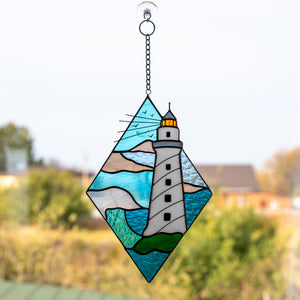 Stained glass rhombus panel depicting a white lighthouse in the waters