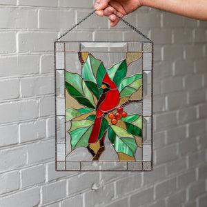 Elegant stained glass panel of a red winter bird sitting on the branch with leaves and berries