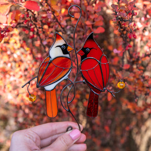 Stained glass red winter birds couple sitting on the branch with leaves and berries suncatcher