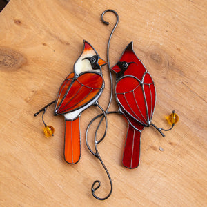Stained glass window hanging of two cardinals in love